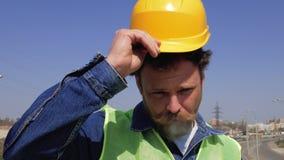 Ένας εργαζόμενος με μια γενειάδα και mustache καπνίζει ένα τσιγάρο και βάζει σε ένα κίτρινο κράνος 4k βίντεο φιλμ μικρού μήκους