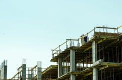 Ένας εργαζόμενος που εργάζεται στην κορυφή του εργοτάξιου οικοδομής οικοδόμησης με το ικρίωμα Στοκ φωτογραφίες με δικαίωμα ελεύθερης χρήσης