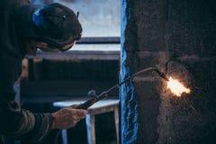 Ένας εργαζόμενος στα προστατευτικά δίοπτρα επεξεργάζεται το γρανίτη με τη συγκόλληση αερίου Στοκ Εικόνες