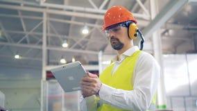 Ένας εργαζόμενος στις σκληρές πληροφορίες τύπων καπέλων και κασκών για τη συσκευή του, που εξετάζει τα αγαθά σε μια αποθήκη εμπορ απόθεμα βίντεο