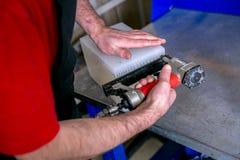 Ένας εργαζόμενος σφραγίζει τη φόρμα για την έκχυση του πλαστικού Κατασκευή των πλαστικών προϊόντων Μέση επιχειρησιακή έννοια Κινη στοκ εικόνα