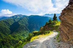 Ένας ευρύς δρόμος με έναν απότομο βράχο οδηγεί κάτω στα υψηλά βουνά Στοκ φωτογραφίες με δικαίωμα ελεύθερης χρήσης