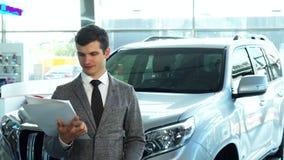 Ένας ευτυχής αγοραστής παρουσιάζει ένα αυτοκίνητο από την αυτοκινητική αίθουσα εκθέσεως στοκ φωτογραφίες