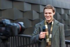 Ένας ευτυχής αρσενικός δημοσιογράφος οδηγεί μια έκθεση σχετικά με τη κάμερα στην οδό στοκ εικόνες