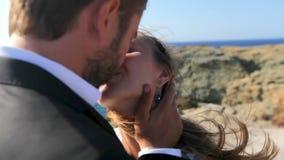 Ένας ευτυχής γαμπρός φιλά τη νύφη στην παραλία σε μια ηλιόλουστη θυελλώδη ημέρα Κινηματογράφηση σε πρώτο πλάνο φιλμ μικρού μήκους