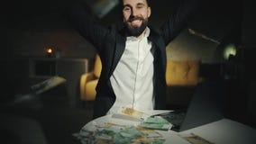 Ένας ευτυχής γενειοφόρος επιχειρηματίας ρίχνει τα μετρητά επάνω στον αέρα αργά στο σπίτι Ένα ενήλικο άτομο είναι ευτυχή, τεράστια απόθεμα βίντεο