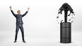 Ένας ευτυχής επιχειρηματίας εκτός από ένα μαύρο βαρέλι με ένα ισχυρό ρεύμα του πετρελαίου που ρέει έξω από το στοκ φωτογραφία με δικαίωμα ελεύθερης χρήσης