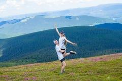 Ένας ευτυχής νεαρός άνδρας κρατά μια γυναίκα υψηλή στα βουνά Στοκ Φωτογραφία