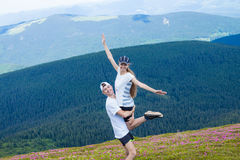 Ένας ευτυχής νεαρός άνδρας κρατά μια γυναίκα υψηλή στα βουνά Στοκ φωτογραφίες με δικαίωμα ελεύθερης χρήσης