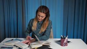 Ένας ευτυχής σπουδαστής σε ένα πουκάμισο τζιν που διαβάζει ένα βιβλίο και που γράφει σε ένα εγχειρίδιο απόθεμα βίντεο