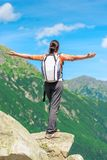 Ένας ευτυχής τουρίστας υπερασπίζεται τον απότομο βράχο στην άκρη του βράχου Στοκ φωτογραφία με δικαίωμα ελεύθερης χρήσης