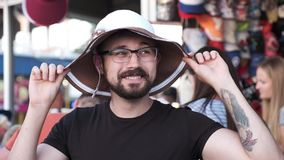 Ένας εύθυμος άνδρας προσπαθεί σε ένα καπέλο γυναικών ` s, κάνει τα αστεία πρόσωπα και ξύνει το κεφάλι του φιλμ μικρού μήκους