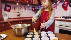 Ένας εύθυμος αρχιμάγειρας κοριτσιών βάζει μια ακατέργαστη ζύμη στη μορφή της Λευκής Βίβλου για το cupcake απόθεμα βίντεο