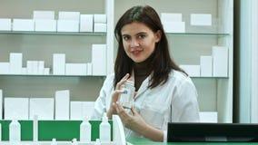 Ένας εύθυμος νέος φαρμακοποιός γυναικών με ένα μπουκάλι των φαρμάκων που στέκονται στο φαρμακείο φαρμακείων που εξετάζει τη κάμερ απόθεμα βίντεο