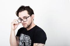 Ένας ελκυστικός νεαρός άνδρας με τα γυαλιά στο άσπρο κοίταγμα υποβάθρου Στοκ Εικόνες