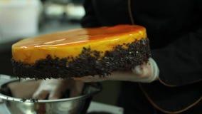 Ένας ζαχαροπλάστης που διακοσμεί τα σύνορα ενός πορτοκαλιού κέικ με τη σοκολάτα ξεφλουδίζει απόθεμα βίντεο