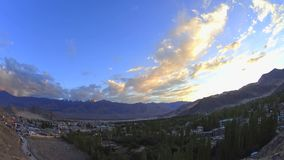 Ένας ζωηρόχρωμος ουρανός ηλιοβασιλέματος σύννεφων χρονικού σφάλματος πέρα από μια πόλη σε μια κοιλάδα βουνών φιλμ μικρού μήκους