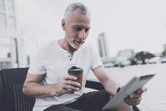 Ένας ηληκιωμένος με μια γενειάδα κάθεται σε έναν καναπέ στην οδό Κρατά τον καφέ και μια ταμπλέτα Στοκ Φωτογραφία