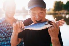 Ένας ηληκιωμένος σε μια μαύρη μπλούζα που θέτει κρατώντας ένα ψάρι Προσποιείται ότι θέλει να την φάει Στοκ Φωτογραφίες