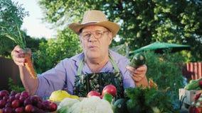 Ένας ηλικιωμένος αγρότης πωλεί τα λαχανικά στην αγροτική αγορά απόθεμα βίντεο