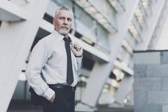 Ένας ηλικιωμένος επιχειρηματίας εξετάζει με βεβαιότητα την απόσταση Στοκ Φωτογραφίες