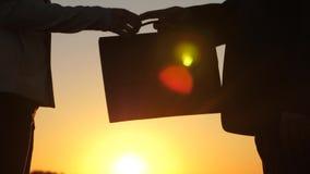Ένας ηλικιωμένος επιχειρηματίας στο σοβαρό κοστούμι με το χαρτοφύλακα στο χέρι του δίνει το σχέδιο εργασίας στη νέα επιχειρησιακή απόθεμα βίντεο