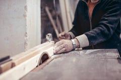 Ένας ηλικιωμένος ξυλουργός πριονίζει ένα ξύλινο κομμάτι προς κατεργασία Στοκ Εικόνα