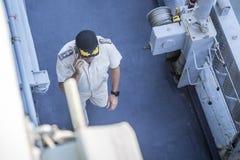 Ένας θαλάσσιος ανώτερος υπάλληλος σε ομοιόμορφο και ένα καπέλο που περπατά κατά μήκος της γέφυρας ενός θωρηκτού του 2009 ο αμερικ στοκ εικόνα με δικαίωμα ελεύθερης χρήσης