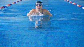 Ένας θηλυκός αθλητής κολυμπά σέρνεται ύφος σε μια λίμνη 4K απόθεμα βίντεο