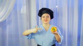 Ένας θηλυκός μάγειρας χαμογελά, κρατά ένα κίτρινο πιπέρι στο χέρι της και δείχνει το απόθεμα βίντεο