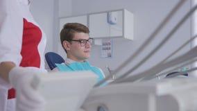 Ένας θηλυκός οδοντίατρος αυξάνει επάνω σε μια οδοντική καρέκλα με έναν νέο ασθενή με τα γυαλιά φιλμ μικρού μήκους