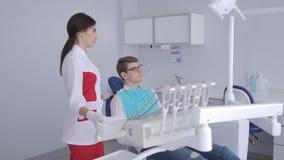 Ένας θηλυκός οδοντίατρος αυξάνει επάνω σε μια οδοντική καρέκλα με έναν νέο ασθενή με τα γυαλιά απόθεμα βίντεο