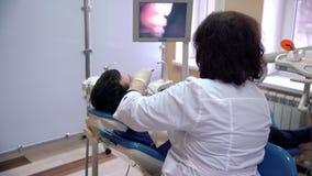 Ένας θηλυκός οδοντίατρος εξετάζει τα υπομονετικά δόντια με μια ενδοστοματική κάμερα και επιδεικνύει τα αποτελέσματα για το όργανο απόθεμα βίντεο
