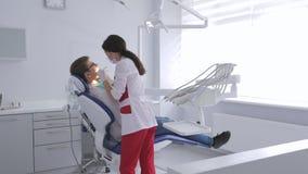 Ένας θηλυκός οδοντίατρος εξετάζει τη στοματική κοιλότητα μιας συνεδρίασης νεαρών άνδρων σε μια καρέκλα φιλμ μικρού μήκους