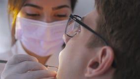Ένας θηλυκός οδοντίατρος εξετάζει τη στοματική κοιλότητα μιας συνεδρίασης νεαρών άνδρων σε μια καρέκλα απόθεμα βίντεο