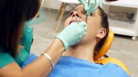 Ένας θηλυκός οδοντίατρος που ελέγχει το τα νέα δόντια γυναικών ` s απόθεμα βίντεο