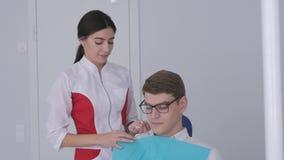 Ένας θηλυκός οδοντίατρος στέκεται δίπλα στην καρέκλα και προετοιμάζει τον ασθενή για μια εξέταση της στοματικής κοιλότητας απόθεμα βίντεο