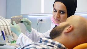 Ένας θηλυκός οδοντίατρος στο hijab που προτείνει υπομονετικό της που χρώμα δοντιών που παίρνει απόθεμα βίντεο