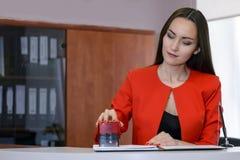 Ένας θηλυκός προϊστάμενος σε ένα φωτεινό κόκκινο επιχειρησιακό κοστούμι βάζει μια σφραγίδα στη σύμβαση στο γραφείο υποδοχής Στοκ εικόνα με δικαίωμα ελεύθερης χρήσης