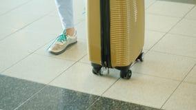 Ένας θηλυκός ταξιδιώτης με μια τσάντα στις ρόδες περπατά κατά μήκος του τερματικού αερολιμένων Στο πλαίσιο μόνο τα πόδια είναι ορ απόθεμα βίντεο