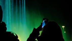 Ένας θηλυκός τουρίστας παίρνει στο τηλέφωνο μια επίδειξη των χορεύοντας πηγών Το νερό χρώματος παρουσιάζει απόθεμα βίντεο