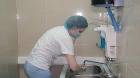 Ένας θηλυκός χειρούργος παίρνει έτοιμος για τη χειρουργική επέμβαση Την πλένει παραδίδει μια ειδική θέση φιλμ μικρού μήκους