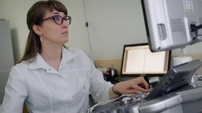 Ένας θηλυκός γιατρός χρησιμοποιεί μια σύγχρονη υπερβολική υγιή συσκευή μελέτης για τα εσωτερικά όργανα Ο υπέρηχος είναι ένας αξιό φιλμ μικρού μήκους