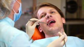 Ένας θηλυκός οδοντίατρος εξετάζει τη στοματική κοιλότητα ενός ασθενή με έναν οδοντικό καθρέφτη απόθεμα βίντεο