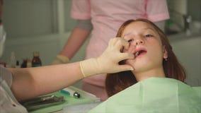 Ένας θηλυκός οδοντίατρος μεταχειρίζεται τα δόντια σε ένα παιδί φιλμ μικρού μήκους