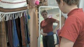 Ένας θηλυκός πελάτης προσπαθεί σε μια μπλε ζώνη απόθεμα βίντεο