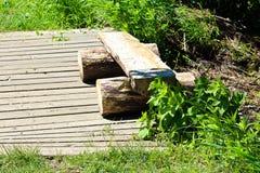 Ένας διασπασμένος ξύλινος πάγκος κούτσουρων σε ένα ίχνος θαλασσίων περίπατων Στοκ Εικόνες