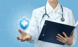Ένας ιατρικός εργαζόμενος κρατά το σύμβολο της προστασίας στοκ εικόνες με δικαίωμα ελεύθερης χρήσης