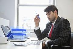 Ένας ινδικός επιχειρηματίας που εργάζεται στο γραφείο γραφείων στοκ εικόνα