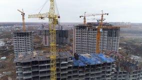 Ένας κίτρινος γερανός πύργων σε ένα εργοτάξιο οικοδομής με πολλά κτήρια απόθεμα βίντεο